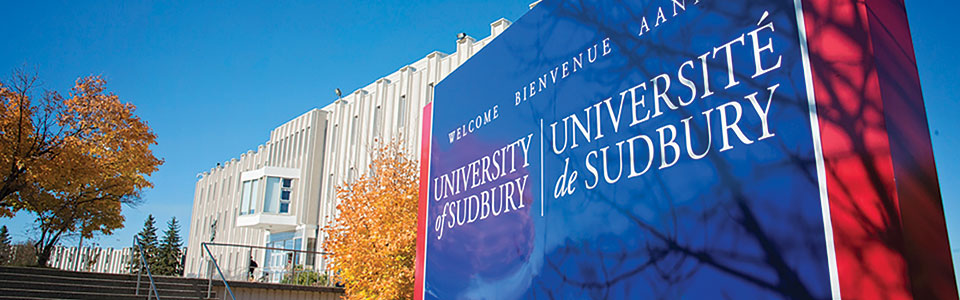 University of Sudbury: students seated on the grounds in front of campus buildings.