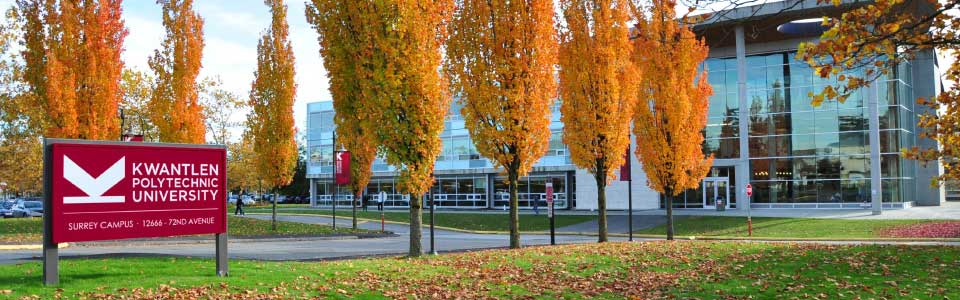 Kwantlen Polytechnic University campus: view of trees in the autumn in front of modern building.