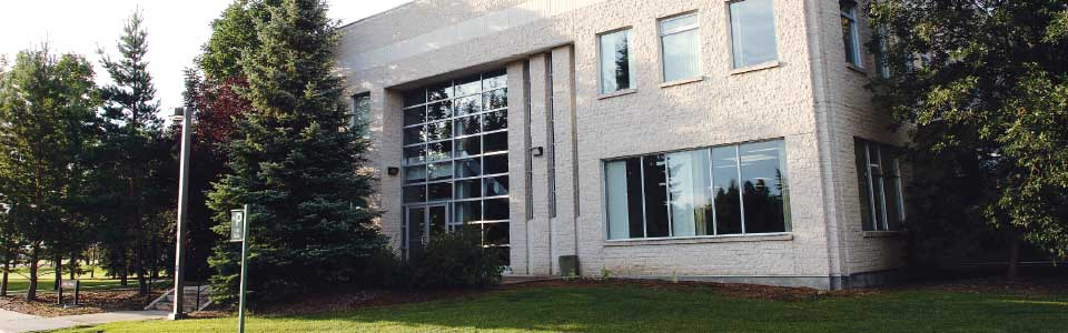 Luther College campus: daytime view of building with trees.