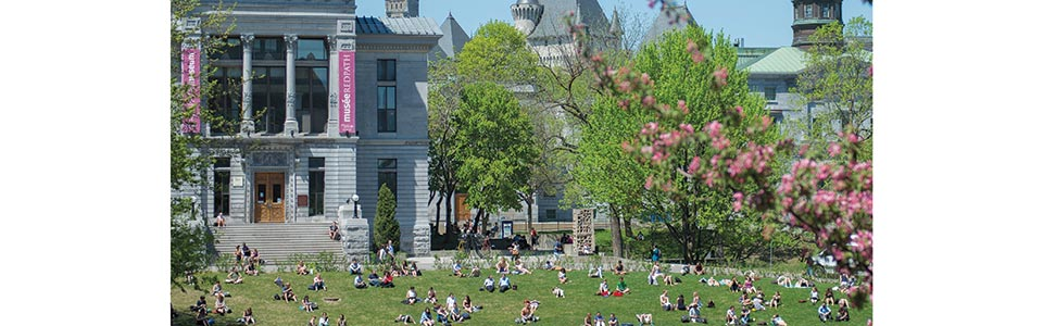 McGill University campus: students sitting on grass in spring in front of building.