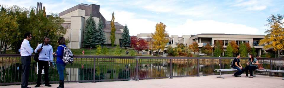 Mount Royal University campus: terrace overlooking water and buildings with students.