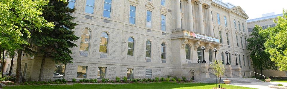 L'Université de Saint-Boniface : bâtiment blanc avec banières universitaires sur le campus.