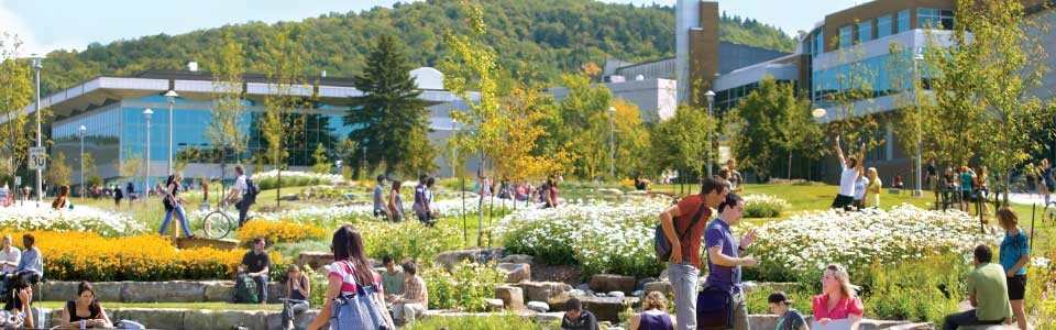 L'Université de Sherbrooke : étudiants et jardin devant bâtiments sur le campus.