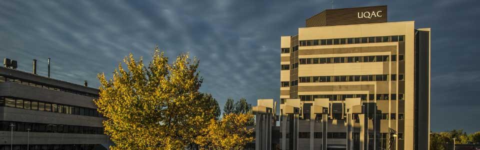 L'Université du Québec à Chicoutimi : ciel foncé et édifice géométrique sur le campus.
