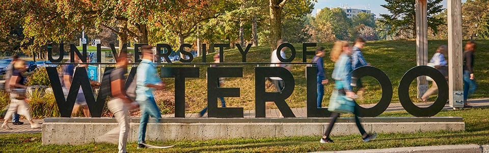 Unversity of Waterloo campus: students walking by large university sign.