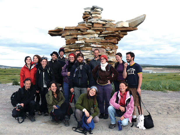 UQAM students in front on a big inukshuk (stone monument) in the North.